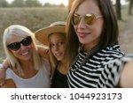 three sisters taking a selfie... | Shutterstock . vector #1044923173