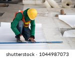Small photo of Construction worker installation water proof membrane in ground floor at construction site