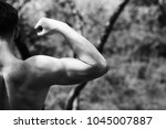 sportsman shows his muscles ... | Shutterstock . vector #1045007887