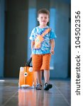Cute little boy with orange suitcase at airport - stock photo