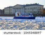 Small photo of ST.PETERSBURG, RUSSIA - MARCH 07, 2018: The boat is MOE from ice blocks from the University embankment at sunset in Saint-Petersburg