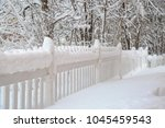 Snow Covered White Picket Fenc...