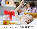 Cute little girl eating spaghetti outdoors - stock photo
