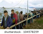 KUKES, ALBANIA, 17 APRIL 1999 -- Kosovar Albanians line up for food between rows of tents at an Italian government-operated refugee camp in northern Albania. - stock photo