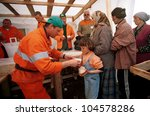 KUKES, ALBANIA,  18 APRIL 1999 --- Italian aid workers feed thousands of Kosovar Albanian refugees at a camp in northern Albania.  Tens of thousands of ethnic Albanians have fled Kosovo. - stock photo