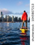 Small photo of Adventurous man is paddle boarding near Downtown City during a vibrant winter sunrise