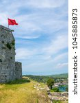 Small photo of Albanian red flag with a black double-headed eagle towers above the fortress of Rozafa.