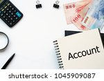 Small photo of Top view white backgorund desktop with Chinese Bank Note Money Notebook write text Account for Accounting concept.