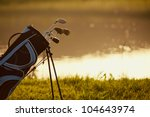 Professional golf gear on the golf course at sunset near the lake - stock photo
