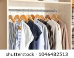 hangers with different clothes... | Shutterstock . vector #1046482513