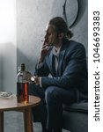 Small photo of alcohol addicted businessman with glass and bottle of whiskey smoking cigarette