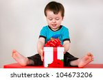 Happy toddler boy opening gift box - stock photo