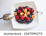 Small photo of On a light background a plate with dessert, next to two spoons of different sizes. Unequal opportunities, initial advantage, additional resource.