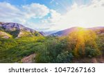Small photo of Mountain chain covered with trees and bushes against blue sky on a sunny day.
