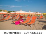 orange umbrellas and chaise... | Shutterstock . vector #1047331813