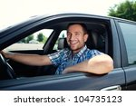 Portrait of young handsome man smiling in his own car - stock photo