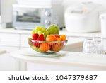 fruit basket in bright kitchen | Shutterstock . vector #1047379687
