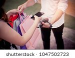 Small photo of A woman uses a use of smart phone to pay for goods with a cashier. Shopping concept.