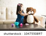 pretty little girl playing with ... | Shutterstock . vector #1047550897