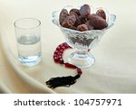 Ramadan breakfast of dates and water with prayer beads - stock photo