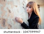 beautiful blonde is standing by ... | Shutterstock . vector #1047599947