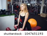 blonde girl posing in the gym.... | Shutterstock . vector #1047651193