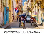 Small photo of HAVANA,CUBA - MARCH 16,2018 : Urban scene with cuban flag and colorful decaying buildings in Old Havana