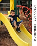 Happy young boy sliding down slide and having fun at outdoor park - stock photo