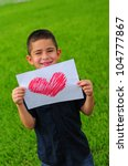 Young boy holding up a gift of a red heart drawing - stock photo