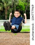 Happy young boy sitting swinging on swing at outdoor park - stock photo