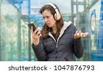 Small photo of marriage, jealousy and suspicion in the cell phone, couple problems, adult woman looking at suspicious messages on the phone while on the street listening to music with headphones