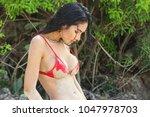 model in a bikini at the beach  ... | Shutterstock . vector #1047978703