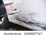 Small photo of insurance agent assessing the damages of a vehicle