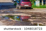 a puddle on a broken asphalt... | Shutterstock . vector #1048018723