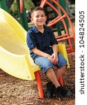 Happy young boy sitting at bottom of slide and having fun at outdoor park - stock photo