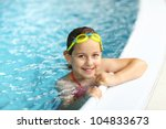 Cute girl with goggles in swimming pool - stock photo
