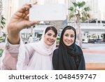 arabic women shopping outdoors... | Shutterstock . vector #1048459747