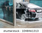 a black car in a lot of foam... | Shutterstock . vector #1048461313