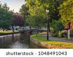 the river windrush flows under... | Shutterstock . vector #1048491043