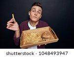 hungry man holding a tray with... | Shutterstock . vector #1048493947