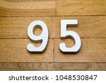Small photo of Figures ninety-five on a wooden parquet floor as a background.