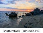 sunset on the beach near... | Shutterstock . vector #1048586543