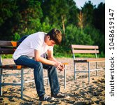 sad guy sit on the bench outdoor | Shutterstock . vector #1048619147