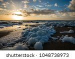 sea foam  on the beach at sunset   Shutterstock . vector #1048738973
