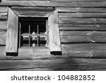 A window with bars in the old wooden house - stock photo