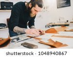 leather craftsman working... | Shutterstock . vector #1048940867