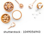 Small photo of Brown and white sugar in bowls, scoop and spoon. Cane, refind, granulated, cubes, candy. White background top view copy space