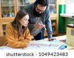 young teacher helping his... | Shutterstock . vector #1049423483