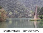 Small photo of The half of suspend bridge and its reflection on the green lake in Yilan, Taiwan.