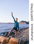 Small photo of boy standing on the sea shore with a stick in his hands in a heroic pose
